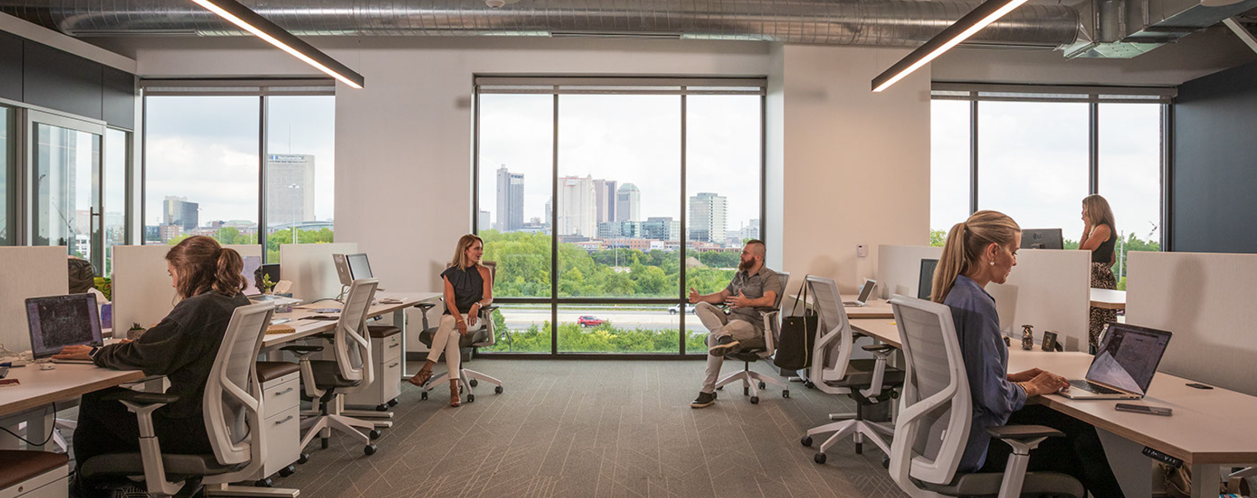 Upright team members working in the office overlooking downtown Columbus.